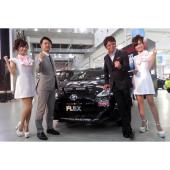 レースクイーンとともに撮影に応じる、俳優の哀川 翔さん(右)と、フレックスの藤崎孝行社長(左)。