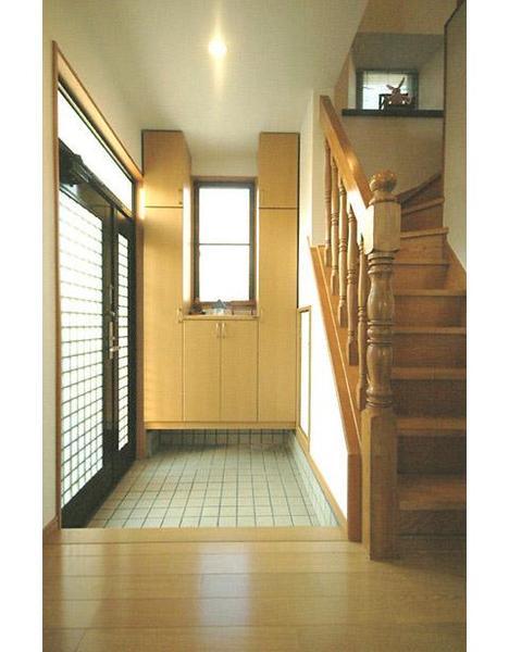 玄関の壁中央にあるサッシから光を。両サイドと下部には大容量の収納が可能