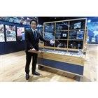 貴重な自動車切手の展示を紹介する学芸員の川島信行氏。世界初の自動車切手は1901年にアメリカで...