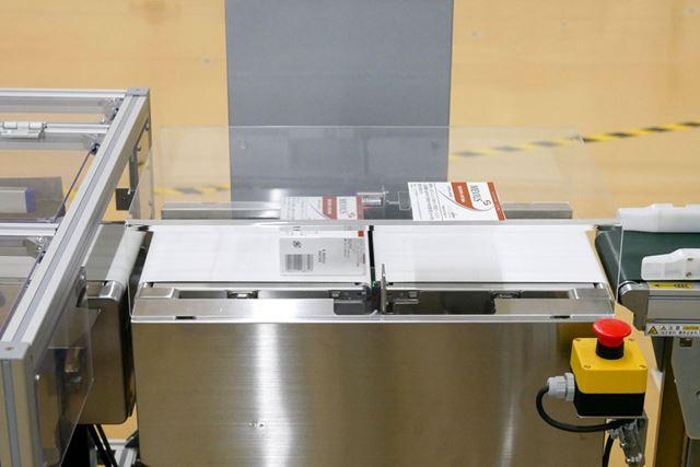 パッケージがカートン化され、重量チェックを経て完成する