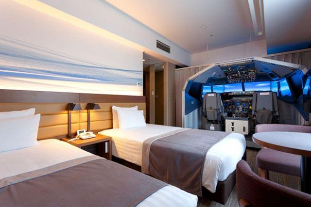 ベッドの横にルームスケールのフライトシミュレーターを備える客室「スーペリアコックピットルーム」