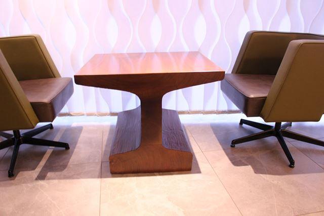 ((上)テーブルはすべて特注品。側面が線路の断面に見えるように加工されたテーブルもある。(下)壁には完成当時の東京駅丸の内駅舎を撮影した写真や、明治時代の上野—青森間の時刻・運賃表のレプリカなども展示されている