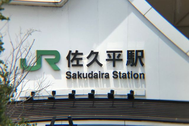 レンズありで撮影した駅名表示。ひさしがゆがんでいたり、街路樹が色収差でにじんでいたりしています
