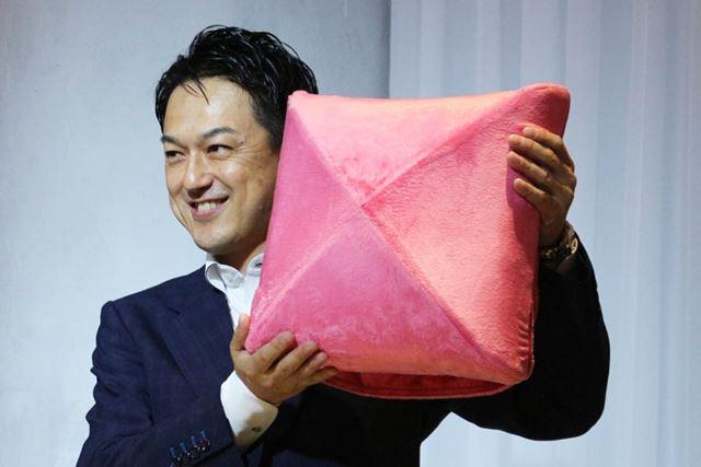 「ルルド マッサージクッション」の初代モデルを掲げる、アテックス 代表取締役社長 深野道宏氏