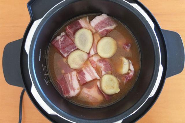 厚さ5�p程度に角切りにした豚バラかたまり肉を鍋に投入。生姜スライスと調味料も加えます