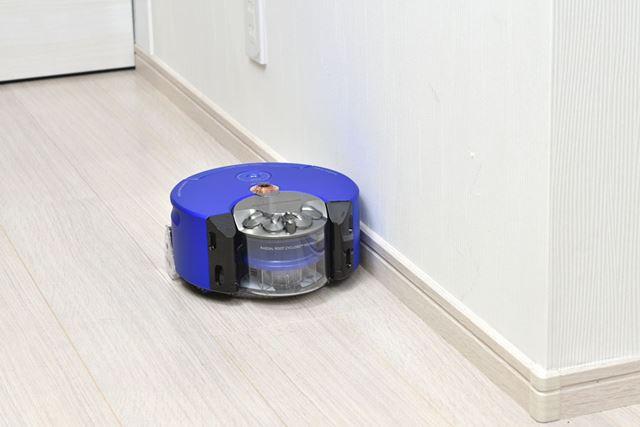 壁にピタリとボディを寄せ、ボディからはみ出すように配置された長いブラシバーでゴミを取り除いていく