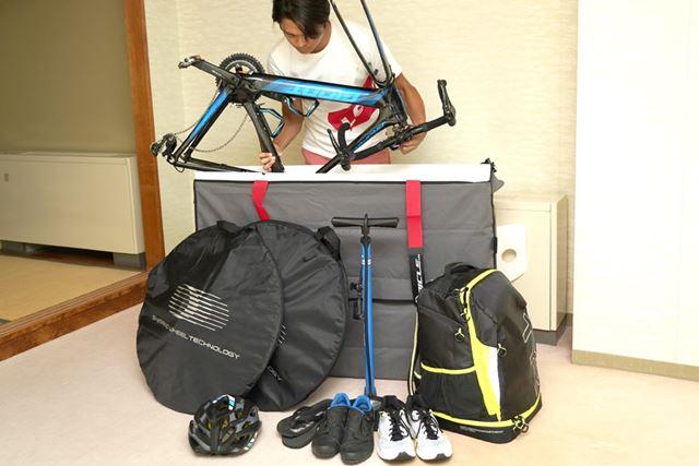まずは自転車の前・後輪を外して、逆さまに入れるのがポイント。そしてそのすき間に荷物を詰め込んでいく