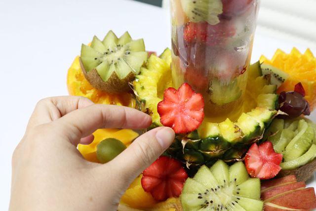 最後に、グラスを土台のパイナップルの上に乗せ、隙間をイチゴとぶどうで埋めていきます