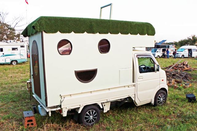 窓が、笑っている顔のように配置されている。人工芝が敷かれた屋根には、車内の天窓から上ることも可能