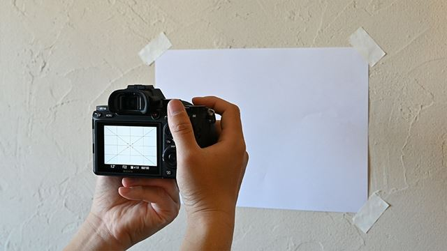 カメラを設定したら、白い壁に向かって撮影します