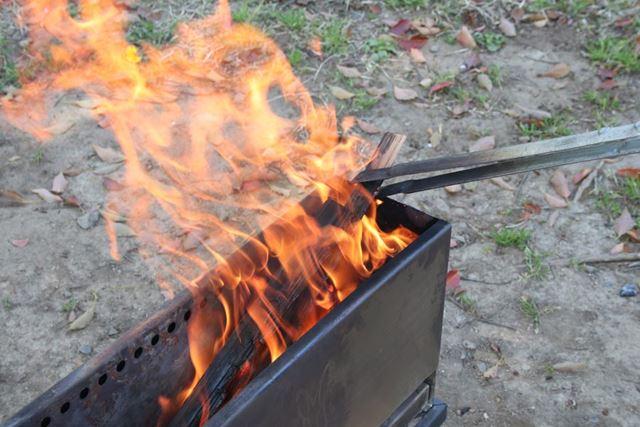全体に火がまわったら、火ばさみを使って薪を倒し、さらに中太の薪を入れます