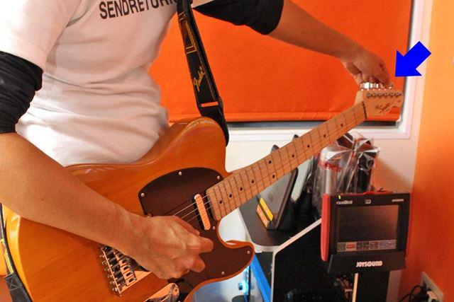 ギターをチューニングしている最中のイメージ。弦をストリングポストに通し、そこからつながっているペグを回すことで弦の張りを調整します