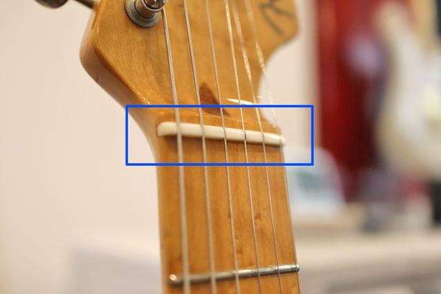 この白いパーツがナットです。ナットに刻まれた溝で弦と弦の幅が確保されています。