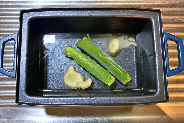 鍋に、水、酒、スライスしたショウガ、長ネギの葉を入れます