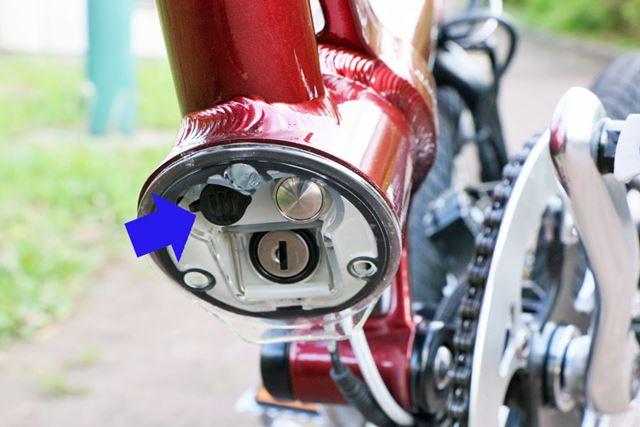 後輪を折りたたむとバッテリーが露出。充電口(矢印の部分)に付属の充電器を接続して充電する